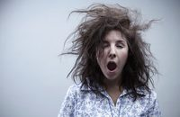 Image of a woman with messy hair, yawning