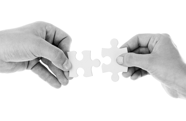 Image of hands holding 2 pieces of jigsaw puzzle