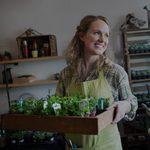Smiling shop owner holding plants