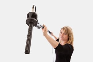 Woman holding a microphone boom against a plain background. Selective focus on the microphone and microphone mount.