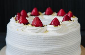 Delicious white cake with strawberries, cream and a pistachio crumb