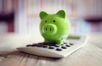 piggy bank on top of a calculator