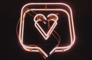 neon pink sign of a heart inside a speech bubble