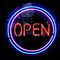 Blue, purple and red neon sign of the word 'Open' inside two circles on neon, on a black background