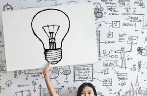Girl holding up a light bulb sign