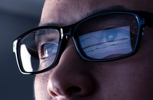 Image of person wearing glasses with screen reflection