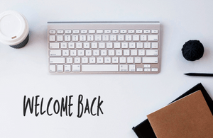 Keyboard on a desk with a note saying welcome back