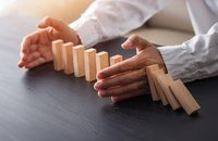 Image of some hands stopping wooden blocks being knocked down