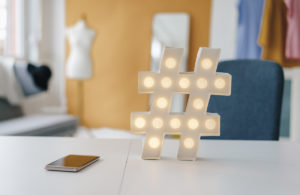 Illuminated hashtag sign on table in fashion studio